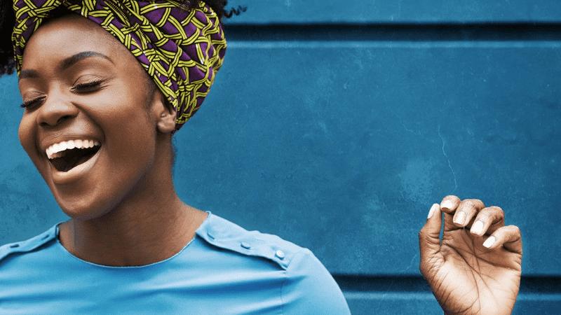 mulher vestindo azul rindo contra uma parede azul