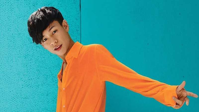 pessoa vestindo blusa laranja contra um fundo azul brilhante
