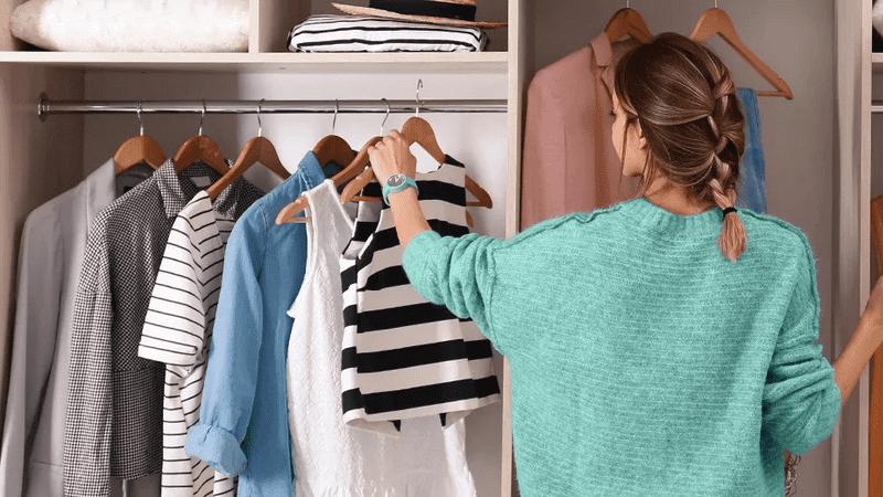 mulher olhando em um guarda-roupa para escolher roupas